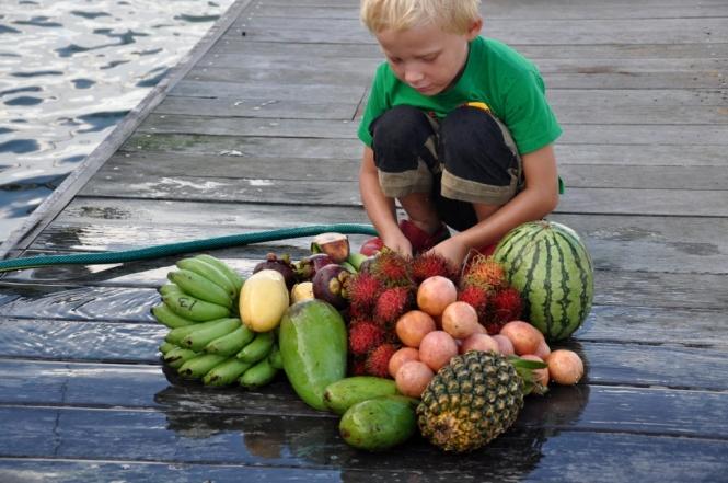 Otto sköljer den färska frukten på bryggan i Malaysia för att bli av med alla insekter. De ljusrosa runda är färska passionsfrukter.